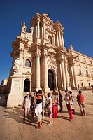 Tourists taking photos in front of the Baroque Duomo cathedral, Syracuse, Sicily, Italy, Europe.