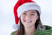A young teen girls dons a santa hat and a big smile.