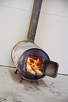 A wood stove in a shop with a fire lit.