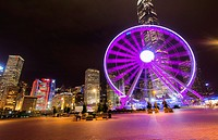 Hong Kong China night skyline with new Ferris Wheel and twilight in city at harbour and Hong Kong Observation Wheel in purple.