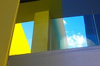 Detail of a building, yellow wall, blue sky and white cloud. Barcelona, Catalonia, Spain.