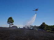 A helicopter with a bag of water cools one of the areas affected by fire in the province of Lugo, Galicia, Spain