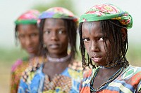 Three Mbororo girls with small scars on their faces looking to the camera.