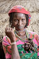 Portrait of a Mbororo woman with scars on her face and many good luck charms around her neck outside her hut.