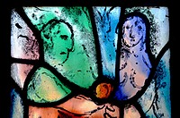 Tudeley, Tonbridge, Kent, UK. All Saints Church. Stained Glass Window by Marc Chagall - Eve offers Adam the forbidden fruit. Visible condensation.