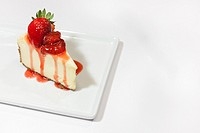 A white cheesecake with dripping strawberry sauce and a graham cracker crust, garnished with whole strawberries on a square plate. Styled with a on a ...