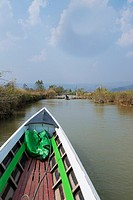 A boat makes its way along a narrow canal from Inle Lake to Indein.