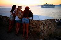People enjoying views of Mykonos town at sunset, Greece.