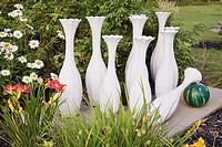 White concrete bowling pin sculptures and green and yellow bowling ball with crimson red Hemerocallis - Daylily and white Leucanthemum vulgare - Ox-ey...
