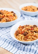 Three bowls of Fusilli pasta, with a tomato meat suace, in white bowls on wodden cutting boards and on a blue checkered napkin.