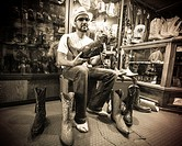 Hispanic man trying on stylish Mexican pointy boots in a store in Oaxaca Mexico.