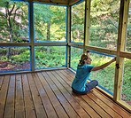 Woman putting blue tape along screens in preparation for painting the posts of a screened porch in a DIY home improvement project.