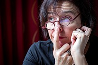 Close-up of middle aged woman with glasses and funny/thoughtful expression
