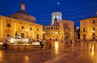 A group of people walk around in the Plaza de la Virgen with the cathedral in background, Valencia, Spain