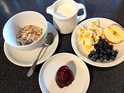 Cereals with oatflakes, fresh blueberries, jam, banana slices half of an apple and a jug with milk