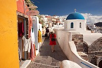 Blue domed church and people walking in the alleys of the Oia village, Santorini, Cyclades Islands, Greek Islands, Greece, Europe.