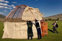 Men in traditional dress assembling wool felt covers over Yurt frame in Saty Kazakhstan.