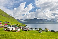 Village Oyndarfjordur, in the background the mountains of the island Kalsoy. The island Eysturoy one of the two large islands of the Faroe Islands in ...