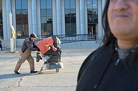 A man pushes his poor people´s car or shopping cart past an indigenous friend of the photographer.