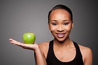 Beautiful healthy happy smiling black asian woman with apple in hand.