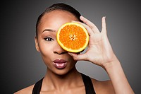 Beautiful healthy happy black asian woman holding delicious orange mandarin fruit in front of eye.