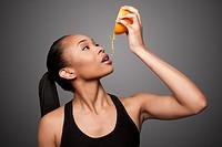 Beautiful healthy happy black asian woman squeezing delicious orange juice mandarin fruit.