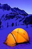 Yellow dome tent at night in winter, John Muir Wilderness, Sierra Nevada Mountains, California USA.