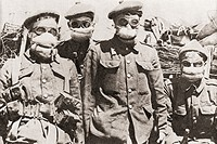 Soldiers in Ypres during World War One using early gas masks, which were pads of cotton wool soaked in a solution of common washing soda. From The Sto...