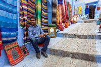 Chefchaouen, Morocco. Vendor of Rugs and Fabrics in the Medina.