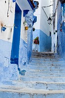 Chefchaouen, Morocco. Berber Woman Walking in the Street between Houses.