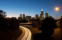 Charlotte North Carolina skyline at night with traffic blurs and twilight.