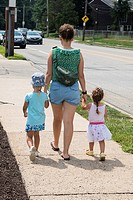 Young woman and two little girls walking by the street, Philadelphia, USA.