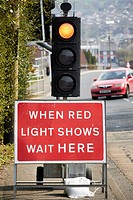 when red light shows wait here sign under temporary traffic lights at road repairs Newtownabbey UK.