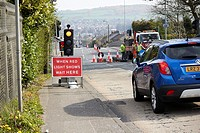 car waiting at when red light shows wait here sign under temporary traffic lights at road repairs Newtownabbey UK.