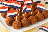 Dutch traditional snack bitterballen on a dish with a dutch flag cocktail stick.