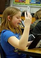 6th Grade Girl Responding to iPad Lesson, Wellsville, New York, USA.