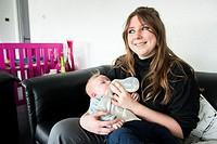 Zwijndrecht, Netherlands. Young adult caucasian mother feeding a bottle of milk to her newborn baby son.