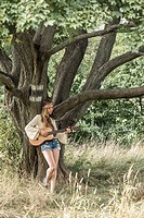 Young singer song-writer musician guitar girl in autumn forest, Vienna, Austria (model-released).