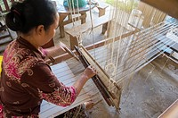 A woman on a loom is weaving silk and cotton fabrics at a workshop in Ban Xang Khong, a village near Luang Prabang in Central Laos, which is known for...