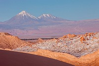 Valle de la Luna (Valley of the Moon ), in background at left volcanoes Licancabur and Juriques with snow on top, and salt deposited on the nearest mo...