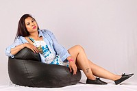 Young girl sitting on a bean bag isolated on white.
