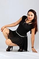 Woman in black dress sitting. Studio shot