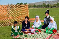 Kazakh family in traditional clothes listening to the music of an accordion player, For editorial Use only, Sati village, Tien Shan Mountains, Kazakhs...