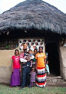 Family standing in front of a traditional painted house, Kembata, Alaba Kuito, Ethiopia.