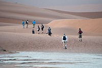 Tourists walking along the sand dunes in the Namib-Naukluft National Park in Namibia, Africa.