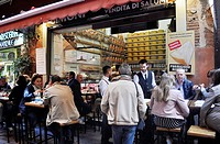 Bologna, Italy: tourists eating at a cold cuts and Parmesan cheese along via Pescherie Vecchie