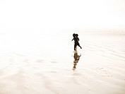 Two free-spirited children run in the hard, wet mud at low tide on a beach. Cape Town, South Africa.