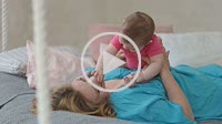 Joyful mother playing with her baby infant in bed