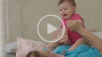 Adorable baby girl laughing in sunny bedroom