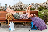 A Woman Reading A Book On A Public Bench, Mandraki Harbour, Rhodes, Greece.